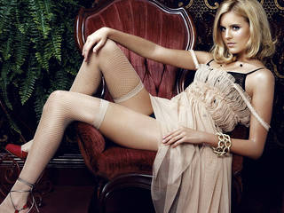 Maggie Grace in stockings and dress.